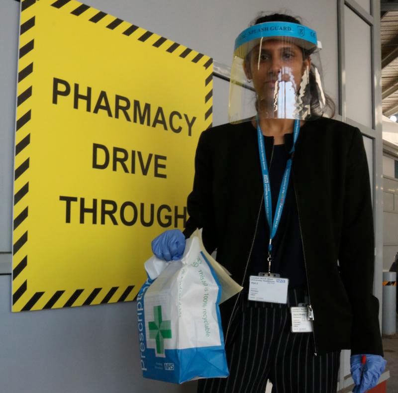 Picture of a pharmacist hold a medicine bag standing in front of a sign to the pharmacy drive through