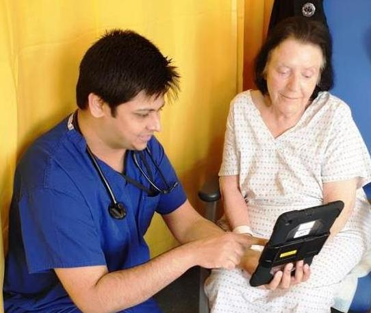 A doctor showing a patient a message on a tablet