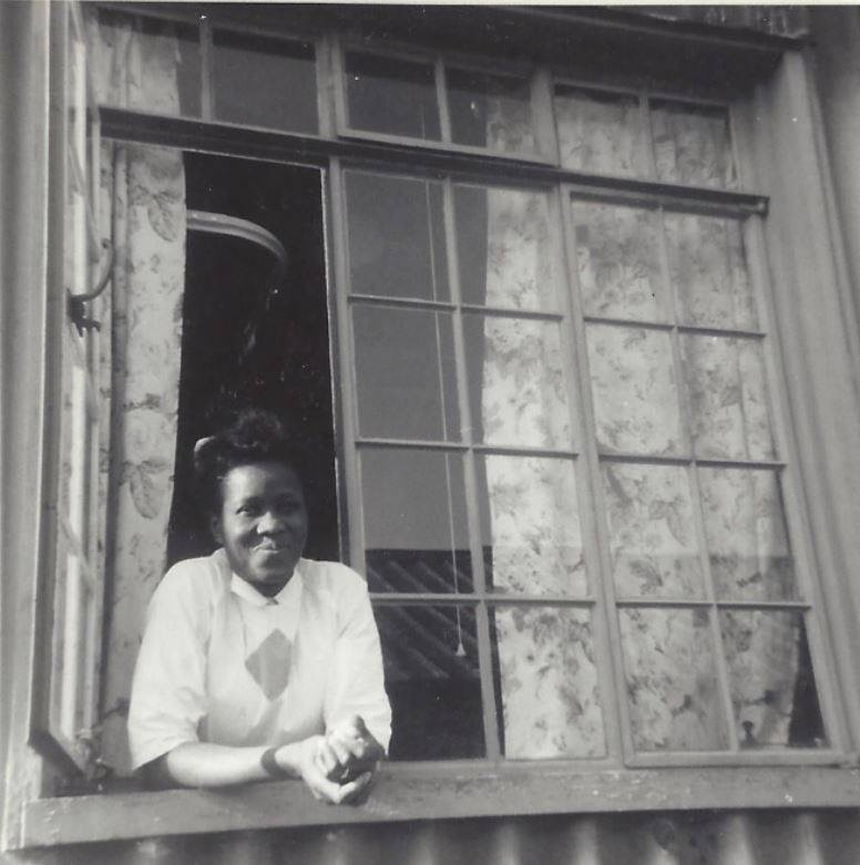 An old photo of a Nigerian lady leaning out of a window